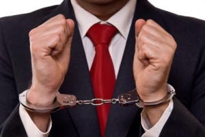 businessman in suit with hands in handcuffs